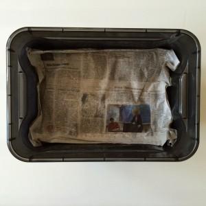 Zeitungspapier mit Sprühflasche mit Wasser anfeuchten