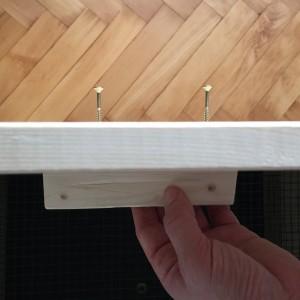 Jeweils zwei Griffe bringen wir mit zwei Spax-Schrauben von außen an die vier Rahmen an.